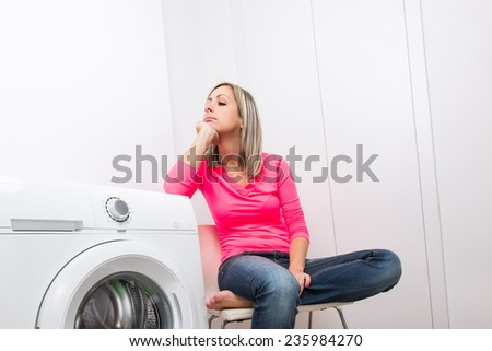 Housework: young woman doing laundry - waiting for the washing program to end - impatient to have her clothes washed, dry and ready to wear (shallow DOF; color toned image) - stock photo