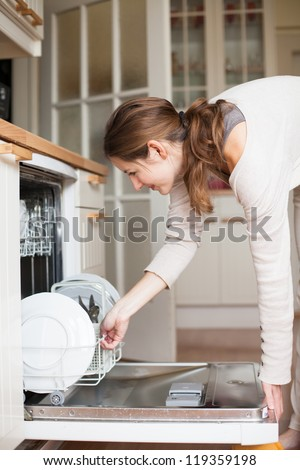 Housework: young woman putting dishes in the dishwasher - stock photo