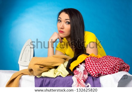 Houseworks, woman with pile of clothes for ironing, on blue background - stock photo