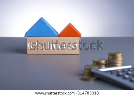 Housing Loan concept. House Wooden Block, coins and calculator with word 0% Interest  - stock photo