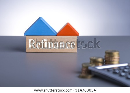 Housing Loan concept. House Wooden Block, coins and calculator with word Refinance  - stock photo