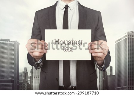 Housing tax on paper what businessman is holding on cityscape background