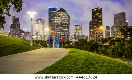 Houston city skyline as night falls and people enjoying Eleanor Tinsley Park