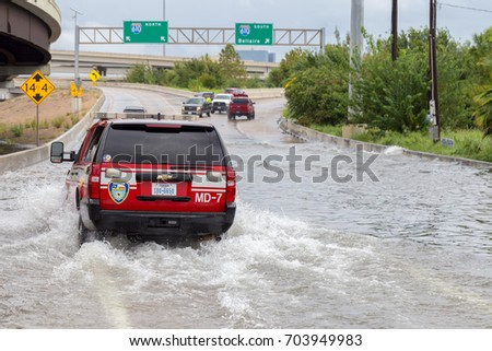 Houston, Texas - August 27, 2017: Houston emergency services cars across the flooded feeder street in Houston, Texas, USA. Heavy rains from hurricane Harvey caused many flooded areas in Houston.