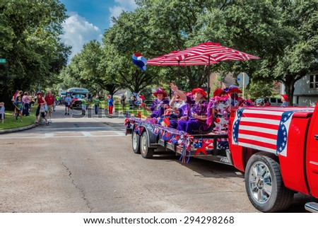 Houston - Texas - July, 4 2015: Neighborhood subdivision  parade with ladies from woman's club riding on trailer.  Red truck is pulling the trailer in Houston, Texas on July 4 2015. - stock photo