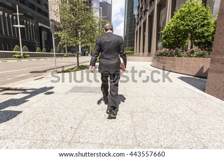 HOUSTON, USA - APR 14, 2016: Businessman in a black suit walking on the sidewalk in downtown district. Texas, United States - stock photo