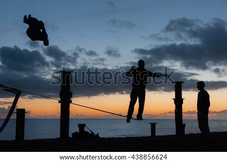HOVE, ENGLAND - JANUARY 19, 2014 - A silhouetted group of people performing acrobatics and walking a slack line on the beach.