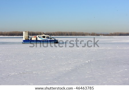 Hovercraft crossing frozen river against a blue sky