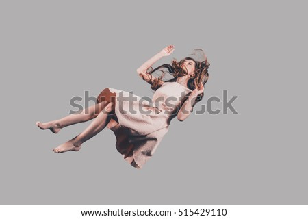 Hovering beauty. Studio shot of attractive young woman hovering in air