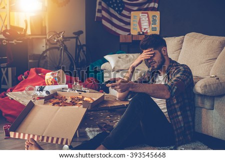 How could I loose? Frustrated young man holding joystick and keeping his hand on forehead while sitting on the floor in messy room after party - stock photo