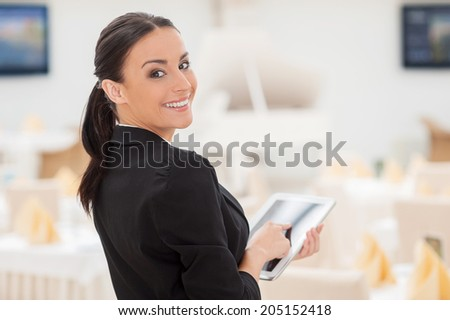 How may I help you? Attractive young woman in formalwear working on digital tablet and looking over shoulder while standing in restaurant - stock photo