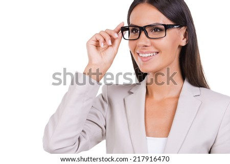 How may I help you? Beautiful young businesswoman in suit adjusting her eyeglasses and looking at camera while standing against white background - stock photo