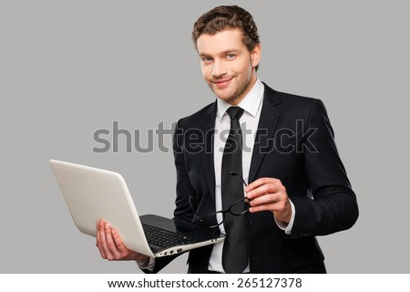 How may I help you? Confident young man in formalwear working on laptop while standing against grey background - stock photo