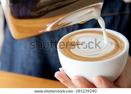 How to free pour a cup of coffee latte - stock photo