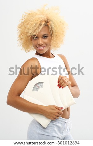 How to maintain proper weight..Young attractive woman with scales. - stock photo