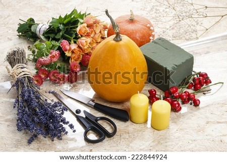 How to make a Thanksgiving centerpiece - step by step: pumpkin, flowers and other objects necessary to make a bouquet in pumpkin - stock photo