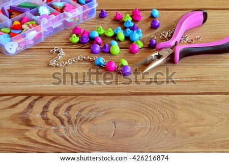 How to make bracelet, fun handicraft for kids. Beautiful way to use buttons. Crafts made with buttons. Diy tutorial. Bright fashion accessory handmade. Open organizer with clothes buttons, pliers - stock photo
