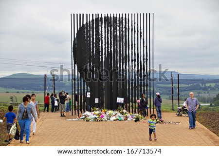 Howick, KwaZulu-Natal, South Africa - 15 December 2013: Mourners gather to pay their respects to the deceased Nelson Mandela at the site where the former political activist was captured in 1962. - stock photo