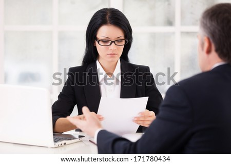 HR director and job candidate. Confident young woman in formalwear holding a paper and looking at it while grey hair man sitting in front of her and gesturing - stock photo