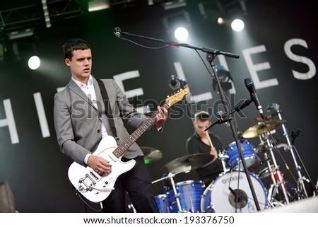 HRADEC KRALOVE - JULY 4: Singer Harry McVeigh (left) of White Lies during performance on festival Rock for People in Hradec Kralove, Czech republic, July 4, 2011. - stock photo