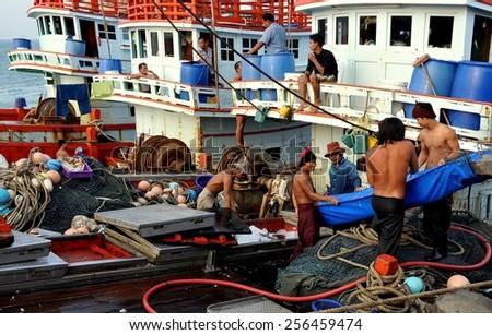 Hua Hin, Thailand - December 31, 2009:  Fishermen loading ice into the hold of their ship docked at the Hua Hin public fishing pier - stock photo