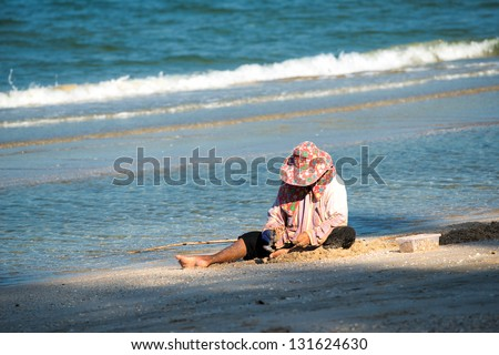 HUA HIN, THAILAND - JANUARY 13: Thai woman picks mussels at the beach on January 13, 2013 in Dolphin Bay outside Hua Hin. Mussel harvesting is an important source of income for many Thai people.