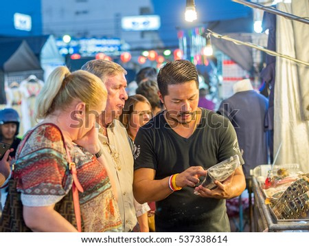HUA HIN, THAILAND - JANUARY 23: Tourists ask about lobster prices at the famous night market on January 23, 2016 in Hua Hin. Hua Hin is a major tourist destination in northern Thailand.