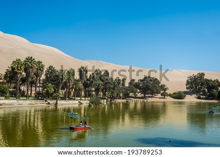 HUACACHINA, PERU - AUGUST 1, 2013: people in run boats at Huacachina lagoon