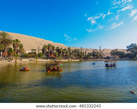 HUACACHINE , PERU - AUGUST 2016 : People in rowing boats in oasis on sunny afternoon