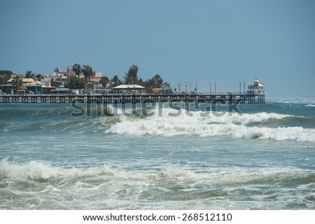 HUANCHACO, PERU - SEPTEMBER 3, 2014: Historic iron pier 108 metres in length at Huanchaco on the coast of northern Peru. Constructed in around 1891. - stock photo