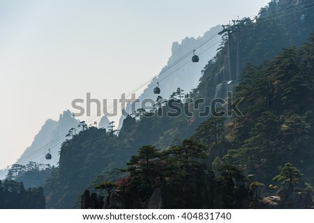 Huangshan Mountain Range - Anhui Province - China. Scenic landscape with a gondola (cable car) moving over steep cliffs and trees during a sunny day. - stock photo