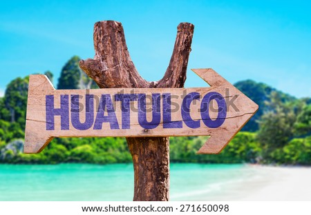 Huatulco wooden sign with beach background - stock photo