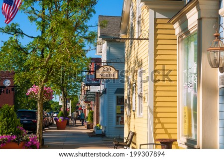 HUDSON, OH - JUNE 14, 2014: Quaint shops and businesses on Hudson's Main Street maintain a charming and inviting appearance that makes it a pedestrian shopper's mecca. - stock photo