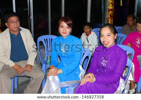 HUE CITY, CENTRAL VIETNAM - DECEMBER 9 : Unidentified women dress in Vietnamese costume style and wait to see the night romance show at The Perfume River on December 9, 2012 in Hue city, Vietnam.