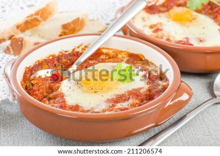 Huevos a la Flamenca (Flamenco Eggs) - Eggs poached in tomato sauce served with bread. - stock photo
