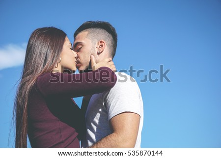 Hug of a romantic couple of teenager in love kissing passionately on a background of sky - Teenage, love and people concept