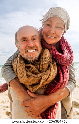 hug two beloved older people enjoying time - stock photo