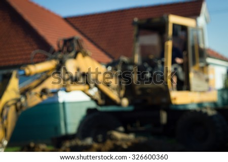 Huge and heavy yellow excavator with shovel standing on the garden near by house (abstract image) - stock photo