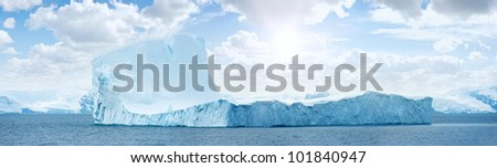Huge antarctic ice island in atlantic ocean. Sunny day. Iceberg.