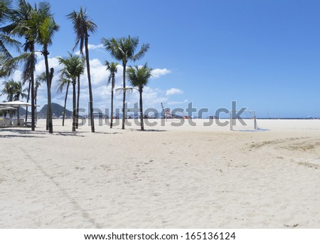 Huge area of sand of Copacabana Beach - some of their coconut trees - sports equipment - people in the background in leisure day - stock photo