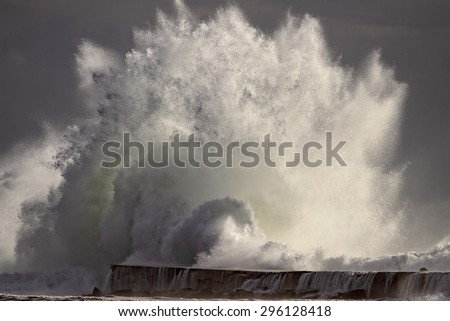 Huge Atlantic stormy breaking wave against pier and beacon of river Ave mouth, Vila do Conde, north of Portugal - stock photo