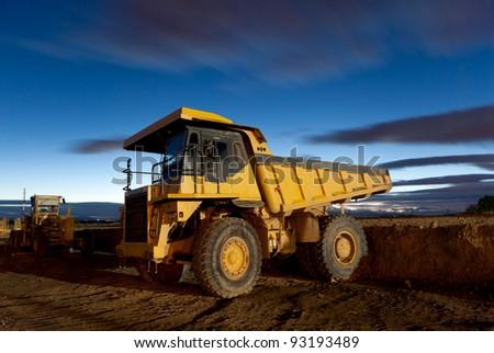Huge auto-dump yellow mining truck night shot and excavator - stock photo