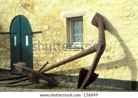 Huge boat anchor laying against stone wall in Ireland