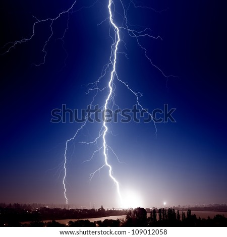 Huge bolt of lightning hits small town - stock photo
