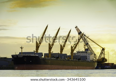 Huge bulk carrier with cranes is waiting for cargo operations in port. Photo taken during sunset. - stock photo