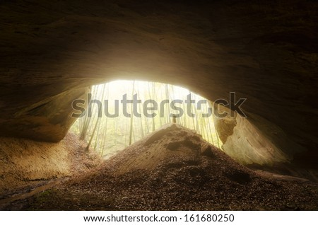 huge cave entrance with man silhouette at sunset - stock photo