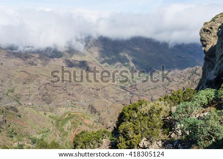 Huge clouds and trade winds from subtropical climate comes from the Azores and reaches La Gomera in approx. 800m altitude. Overlook from the Mirador de La Laja to the canyon Barranco de la Laja, - stock photo