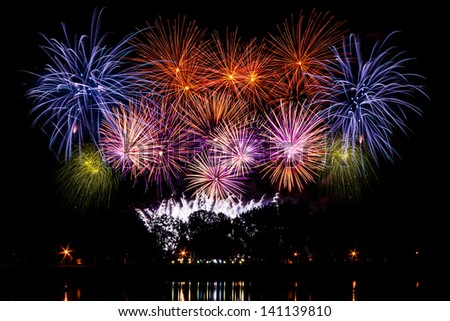 Huge colorful fireworks against the night sky - stock photo