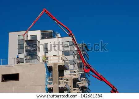 Huge concrete pump with tall arm pumping conrete on top of the building with unrecognizeable workes - stock photo