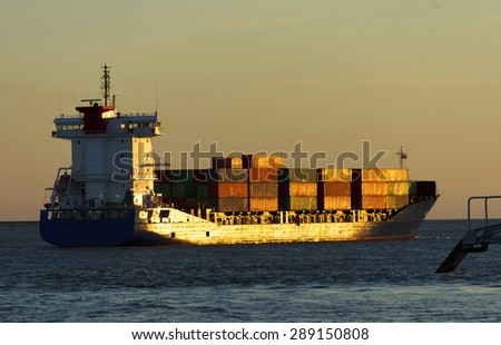 Huge container cargo ship in sunset light - stock photo